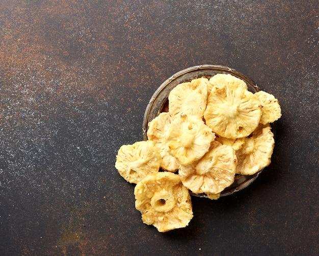 乾燥した砂糖漬けのパイナップルリング。茶色のコンクリート背景に甘い果物をスライスしました。上面図。