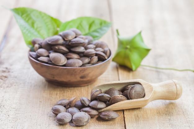 Сушеные семечки семян плодов sacha inchi арахиса на деревянных