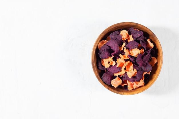나무 그릇에 말린 당근과 비트 칩과 생 당근, 흰색 콘크리트 배경에 비트.