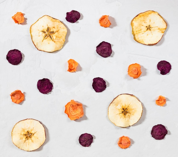 Dried carrot, beet, apple chips on a white concrete background.