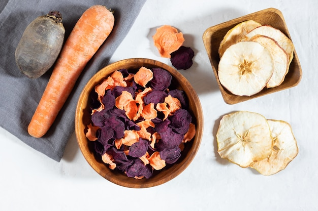 Dried carrot and beet chips in a wooden bowl and raw carrots, beets on a white concrete background.