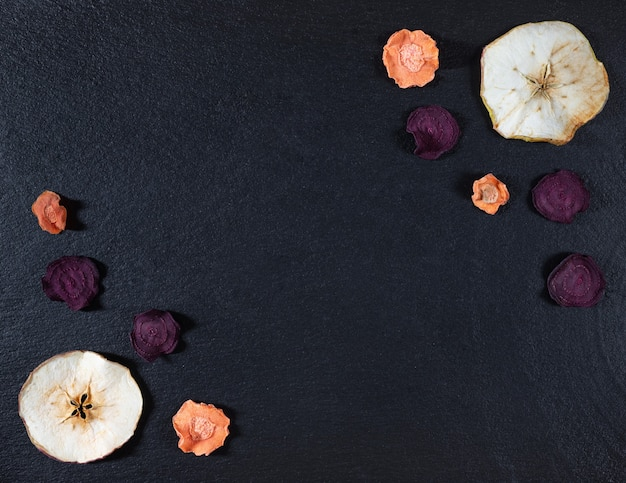 Dried carrot, beetroot and apple chips on a black stone background.