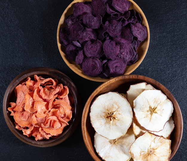 Dried carrot, beetroot and apple chips in a wooden bowl on a black stone background.