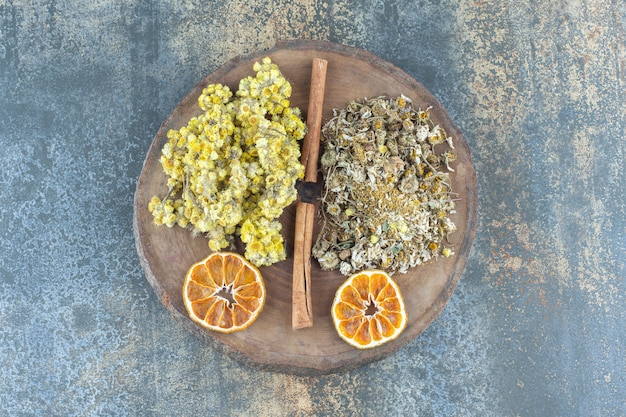 木片に乾燥したカモミールと菊。