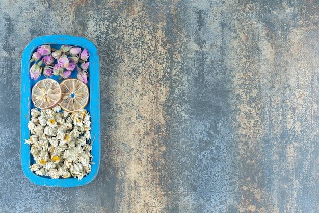 Camomilla essiccata e rose in erba sul piatto blu.