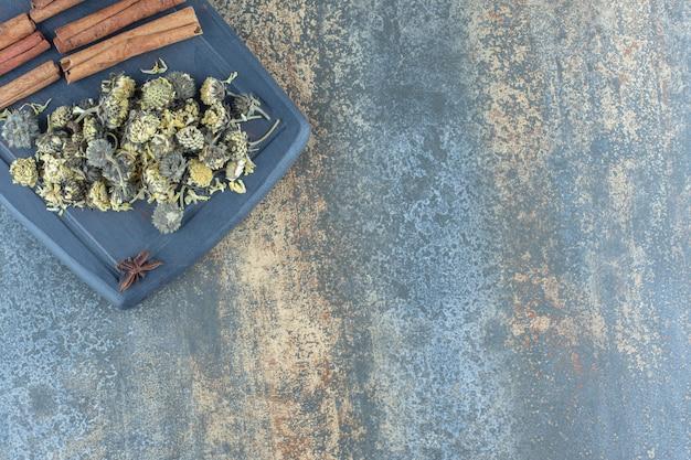 Camomilla essiccata, bastoncini di cannella su tavola scura.