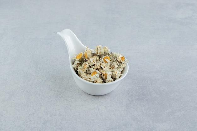 흰 그릇에 말린 카모마일 꽃.