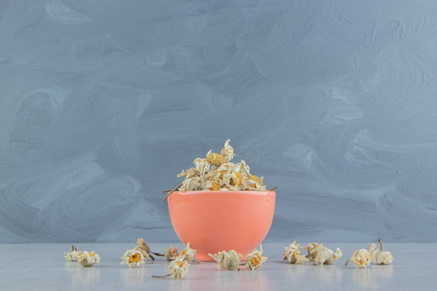 Dried chamomile flowers in orange bowl.