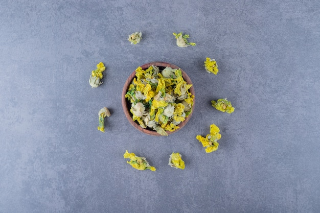Dried chamomile flowers in wooden bowl over grey.