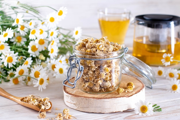 白い木製のテーブルの上の瓶にカモミールを乾燥させた。カップと花のオーガニックカモミールティー