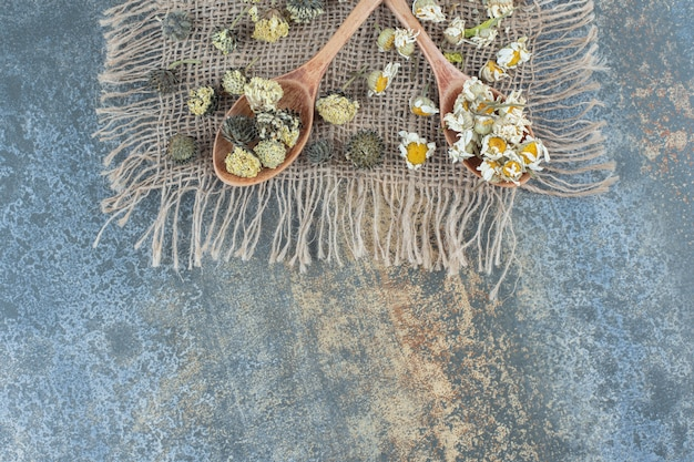 Dried chamomile and other flowers on burlap with wooden spoons.