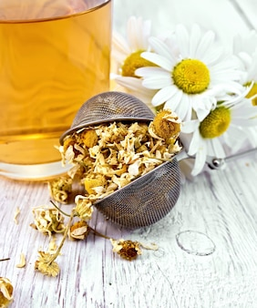 Dried chamomile in strainer, cup with herbal tea on a background of light wooden boards