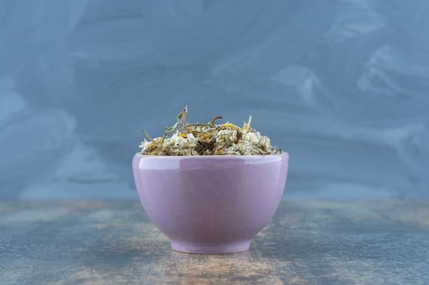 Сушеный ромашковый чай в фиолетовой миске.