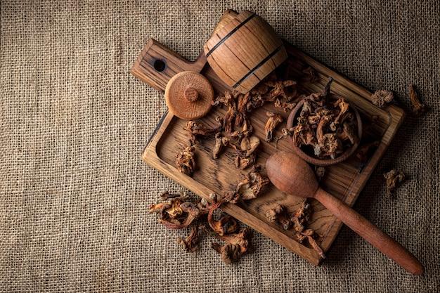 """Сушеные лисички (cantharã """"llus cibã"""" â rius), на деревянной доске, на шероховатой тканой поверхности, мешковине, вид сверху"""