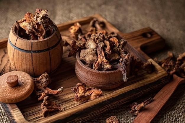 """Сушеные грибы лисички (cantharã """"llus cib"""" â rius), на деревянной доске, на шероховатой тканой поверхности, мешковине."""