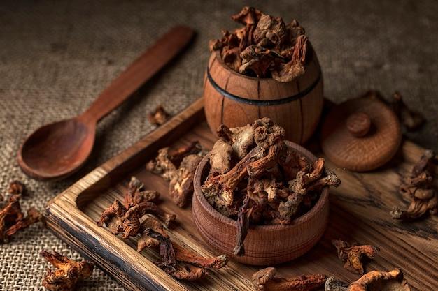 Сушеные грибы лисички, на деревянной доске деревянной ложкой и деревянной бочкой