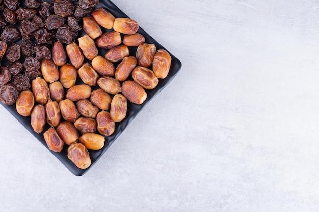 말린 체리, 딸기 및 날짜는 나무 접시에. 고품질 사진
