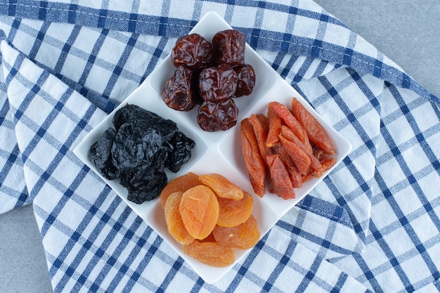 Dried cherry, apricot, plum in the bowl, on the tea towel, on the marble table.