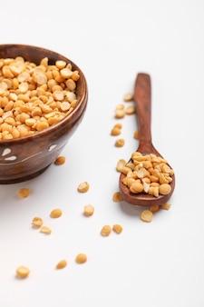 木製のボウルと白い背景の上のスプーンでひよこ豆レンズ豆を乾燥、分割ひよこ豆はチャナダルとも呼ばれます