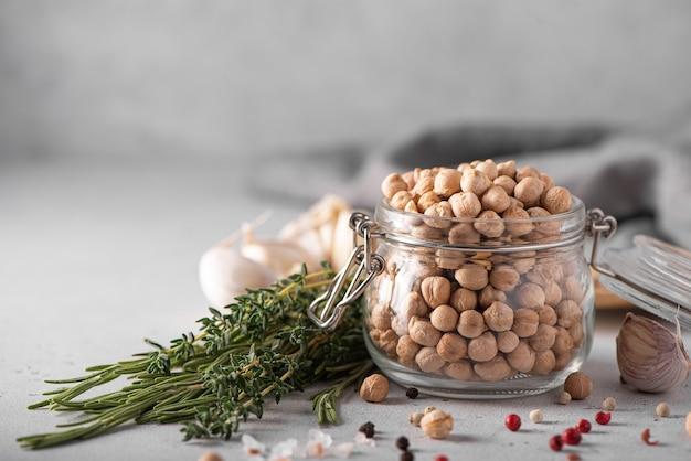 白いテーブルの上のハーブとスパイスとガラスの瓶で乾燥したひよこ豆