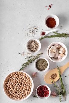 スパイスとハーブを入れた白いボウルにひよこ豆を乾燥させた