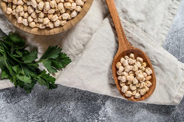 木のスプーンでひよこ豆を乾燥させます。健康的なベジタリアン料理。灰色の背景。上面図