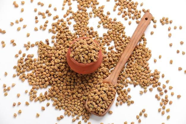 白い背景で隔離のボウルに乾燥ひよこ豆。