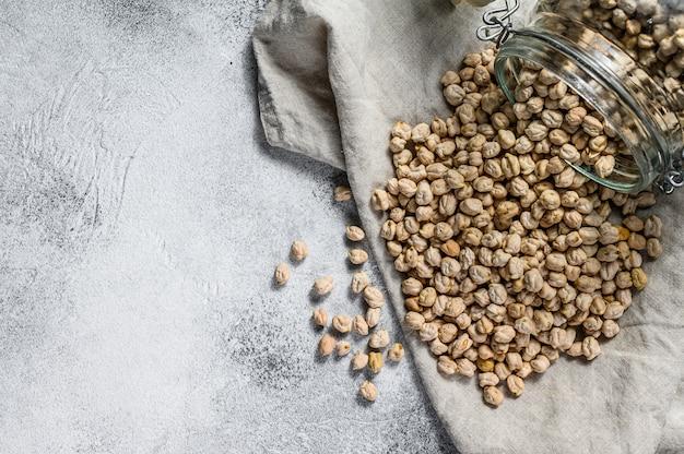 ガラスの瓶からひよこ豆を注いだ。健康的なベジタリアン料理。灰色の背景。上面図。テキスト用のスペース
