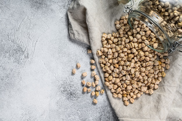 Dried chickpeas poured from a glass jar.