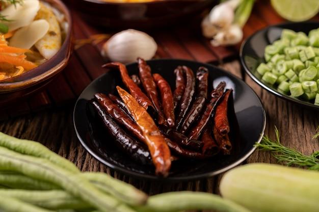 レンズ豆と一緒に黒い皿で揚げた乾燥唐辛子きゅうりとにんにくを木製のテーブルに置きます。