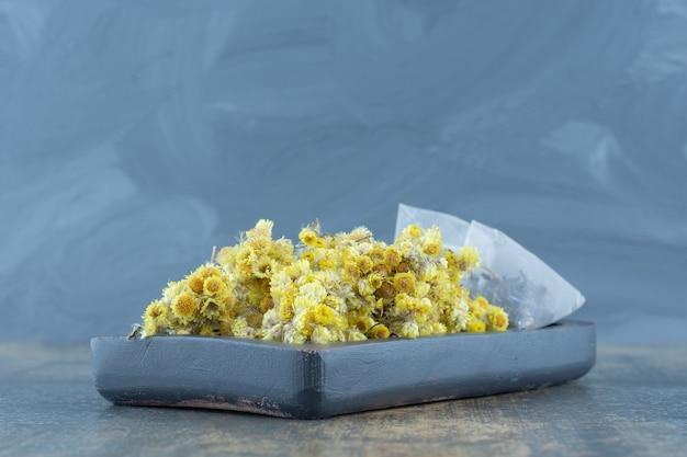 Сушеные хризантемы и пакетики чая на темной тарелке.
