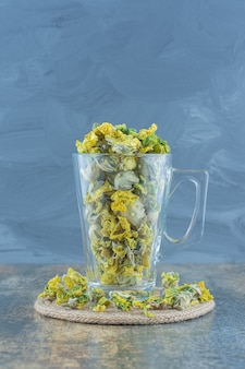 Dried chrysanthemum flowers in glass on blue background.