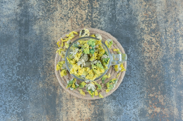 Fiori di crisantemo secchi in vetro sul tavolo blu.