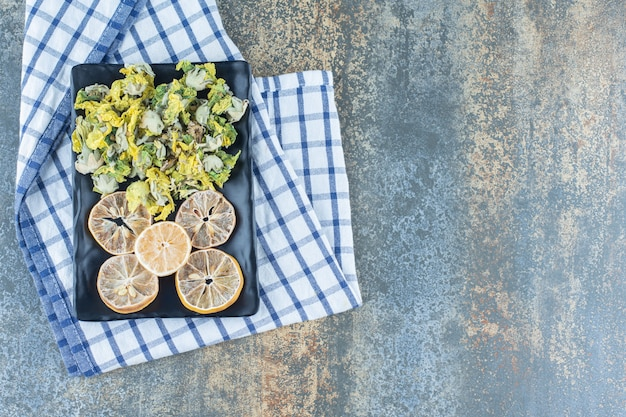 Crisantemo essiccato e fette di limone sulla banda nera.