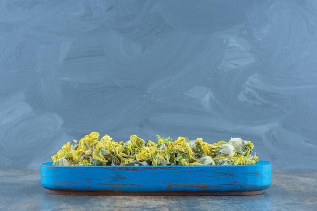 Petali secchi del crisantemo sul piatto blu.