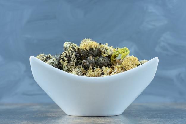 Высушенные лепестки хризантемы на белой тарелке.