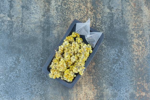 Dried chrysanthemum and teabags on dark plate.