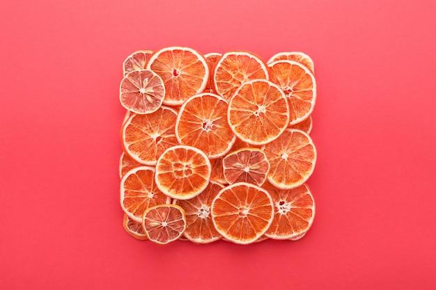 乾燥した柑橘類がレモンとオレンジをコーラルピンクにスライスします。
