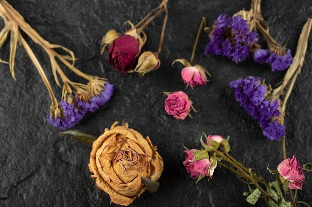 黒いテーブルの上で乾燥した色とりどりの花。