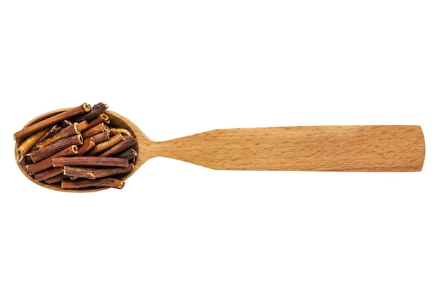 Dried comarum palustre in a wooden spoon on a white background.