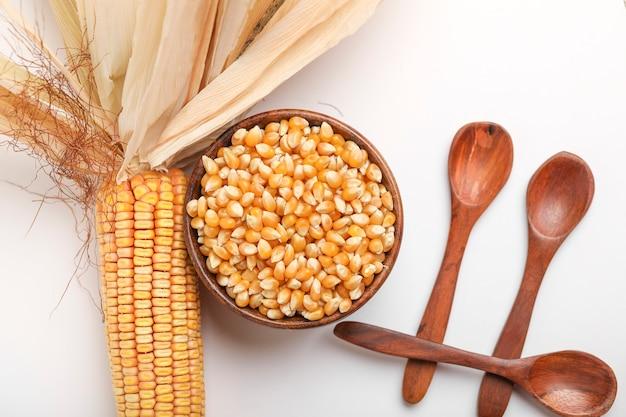 Сушеные семена кукурузы в миске на белом фоне