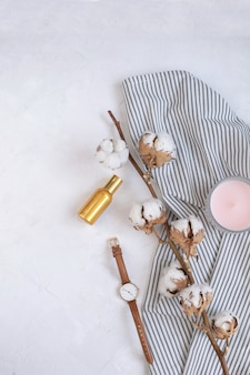 Dried cotton branch, candle, perfume bottle, watch on crumpled striped napkin
