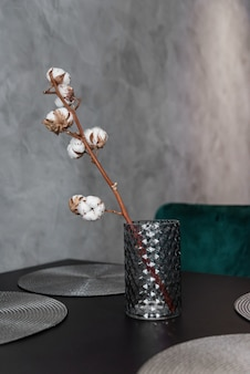 Dried cotton branch in stylish ceramic vase stands on black kitchen table