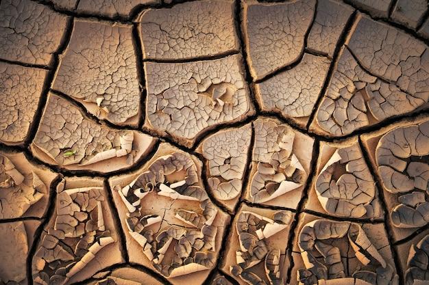 乾燥したひびの入った土の地面のテクスチャの背景。日当たりの良い乾燥した土のモザイクパターン
