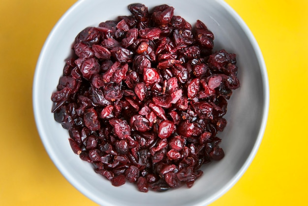 Dried cranberries in white bowl. ingredients for healthy breakfast.