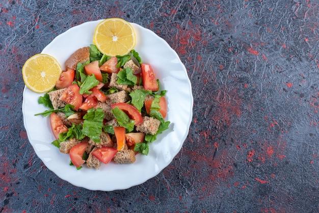Сушеная корочка, смешанная с овощным салатом с лимонным гарниром на темном фоне. фото высокого качества