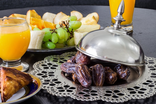 Dried date medjool palm fruits, fresh orange juice, samosa snack and fruit background concept iftar in the holy month ramadan