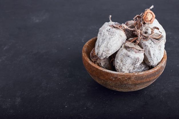 灰色の表面に木製のカップで乾燥したナツメヤシ。