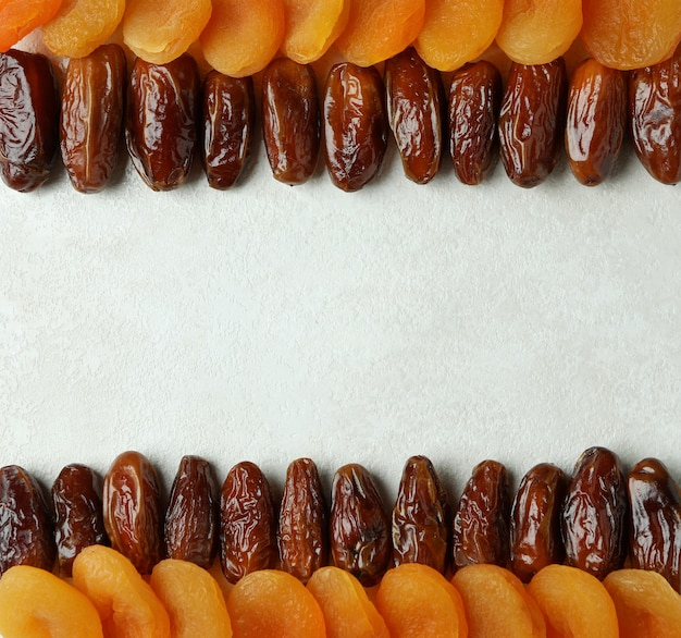 Dried dates and apricots on white textured surface