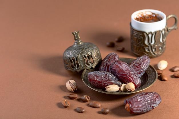 乾燥ナツメヤシは、伝統的なブロンズ料理のアラビアブラックコーヒーに人気のデザートで、厳選されたものです。空間のコピーのある静物。